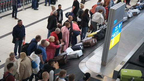 Alanya, Turkey - May, 2, 2017: Airport, baggage claim. Many suitcases and bags are passing by the conveyor belt past the tourists who dismantle their luggage. People flew by plane on vacation.