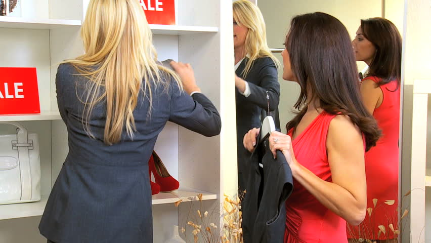 Young boutique owner showing designer outfits to Caucasian brunette client