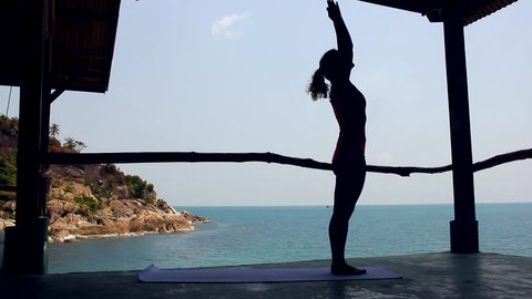 Silhouette of young woman practicing yoga doing surya namaskar asana, known as sun salutation pose on platform by the sea in the island of Koh Pha Ngan, Thailand