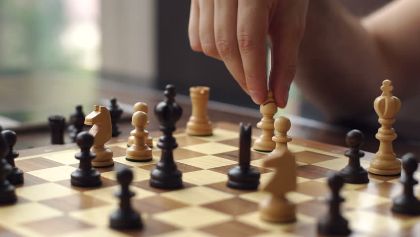 Close-up of the hand of a man playing chess. Close-up of man who is making move in chess game. Man and woman playing chess in a cafe. Slow motion.