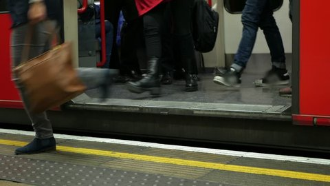 People getting off a tube train in London. A tube train on the London Underground stopping at a platform, the door opens and people get off.