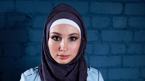 A portrait of a modern Muslim woman who wears a hijab and a leather jacket, a young woman with painted eyes looks into the camera. Arab woman is fashionably dressed