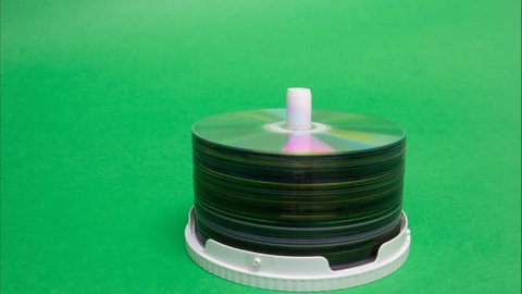 Closeup of a stack compact discs on green background. Cd and dvd moving up and down. Stop motion animation.
