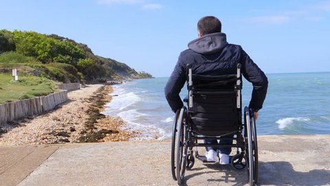 Back of alone disabled young man in wheelchair at beach.