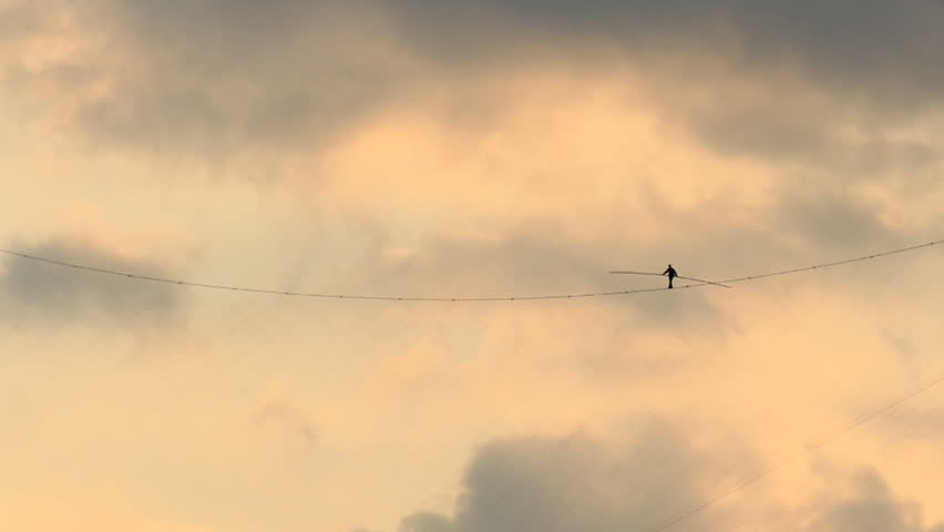 Tightrope Walker Sky Timelapse. Someone walking a tightrope high in the sky. Shot in time-lapse with a beautiful sunset in the background.