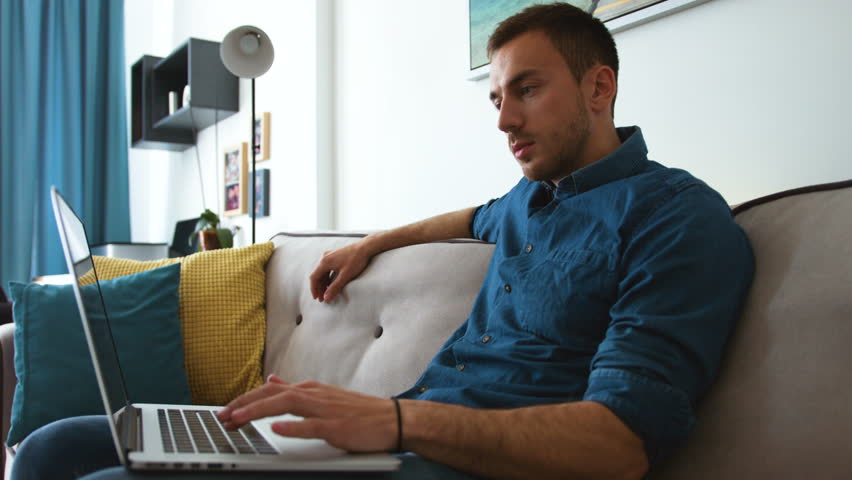 Young attractive man sitting on the couch and using laptop, clicks on the keyboard at home | Shutterstock HD Video #27119053