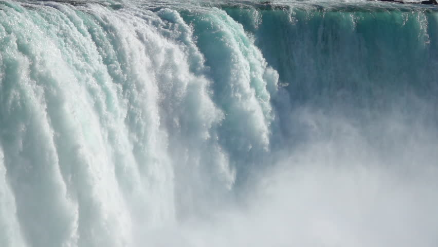 SLOW MOTION, CLOSE UP: Powerful raging whitewater waterfall falling forcefully over a rocky edge. Crystal clear glacier water stream dropping over the cliff. Misty majestic Niagara Falls river rapids | Shutterstock HD Video #27121114