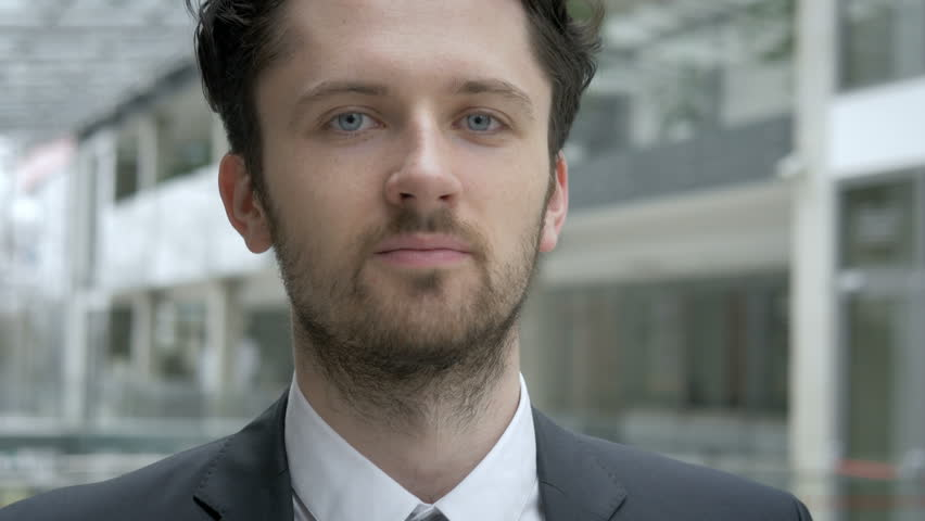 Close-up of young professional in suit looking at the camera. Successful male worker in the modern office building.