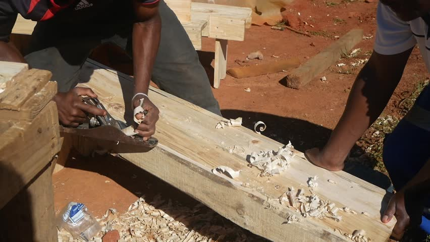 RICHMOND KWAZULU-NATAL/SOUTH AFRICA - MAY 2 2017: A black rural hardworking carpenter plane a plank with a planer.