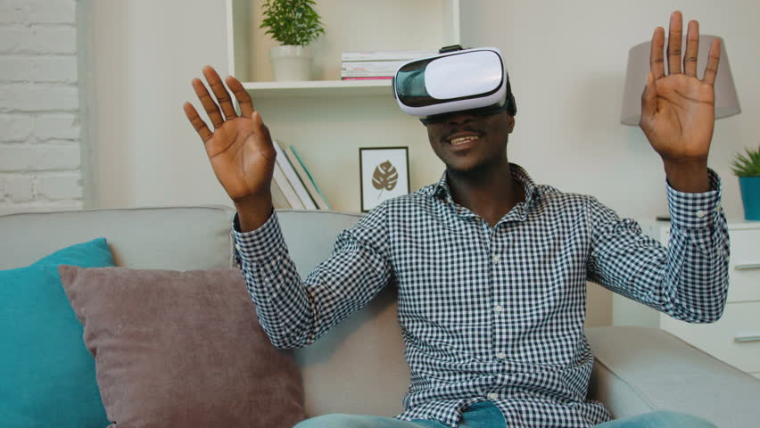 Black african american man using vr headset at the couch in the living room. Exited man looking aroung and touching virtual objects | Shutterstock HD Video #27170314