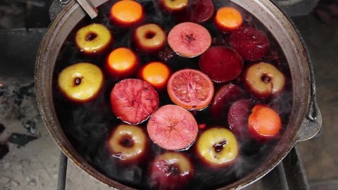 Big copper in which mulled wine at Christmas fair cooks. Mulled wine with fruit and spices cooked in a large pot, over which there is a vapor.