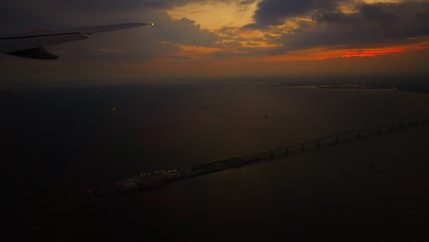 Aerial view of sunrise through airliner window. Aerial view of Cloudscape in dawn through plane window. Landing to Tokyo, Japan. Beautiful trip with good transportation concept.   Shutterstock HD Video #27186694