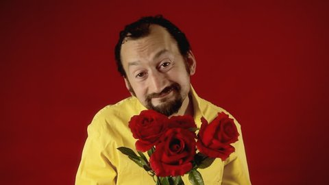 A funny ugly man offers a handful of red roses to the viewer. Valentine's day, dating, anniversary, unexpected, unwanted.