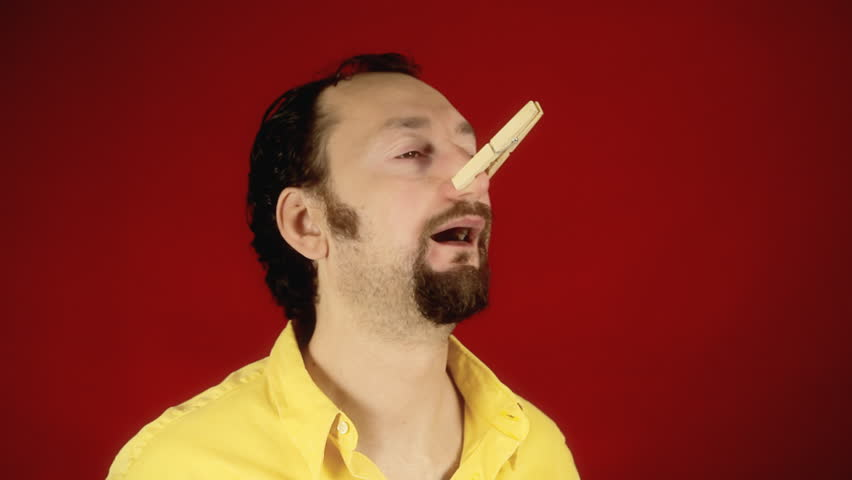 A funny guy smelling a bad stink or foul odor and closing his nose with a clothespin, finally finding the peace of mind.