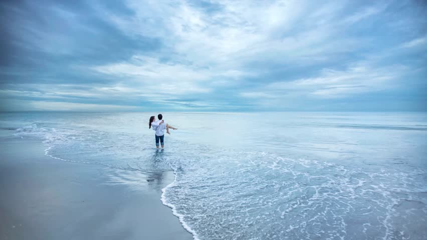 4K resolution Cinemagraph, Couple honeymoon in love, a Man is holding a woman on the beach, romantic in love background.