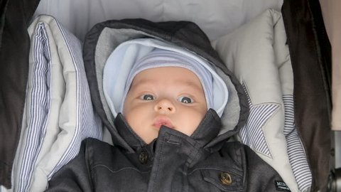 infant lies in a sidecar, with a hat and hood in the spring