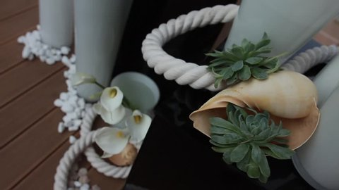 Nautical party decoration: tall white glass vases with white calla flowers on wooden floor, green succulent plants on white ship rope and big spiral seashell on black glass box in slow motion.