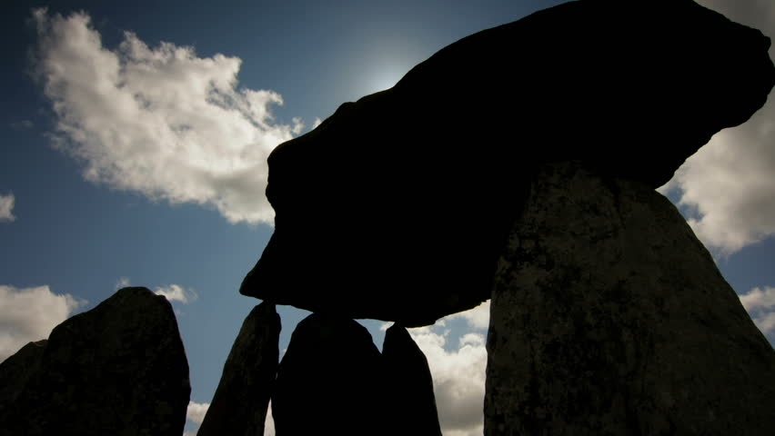 Silhouette of Pentre Ifan; an ancient burial chamber from 3,500 B.C, located in Pembrokeshire, Wales. Tracking time lapse. Sunny day.