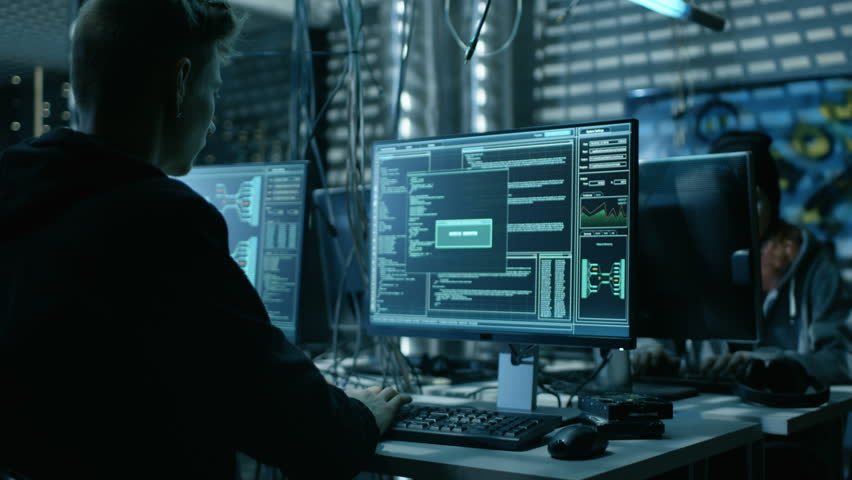 Young Hacker Breaks into Corporate Data Servers from His Underground Hideout. Place Has Dark Atmosphere, Multiple Displays, Cables Everywhere. Shot on RED EPIC-W 8K Helium Cinema Camera.