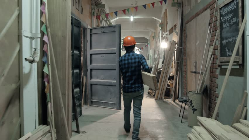 Carpenter doing his job in carpentry workshop. Man walking on factory with plywood, furniture manufacture   Shutterstock HD Video #27247954