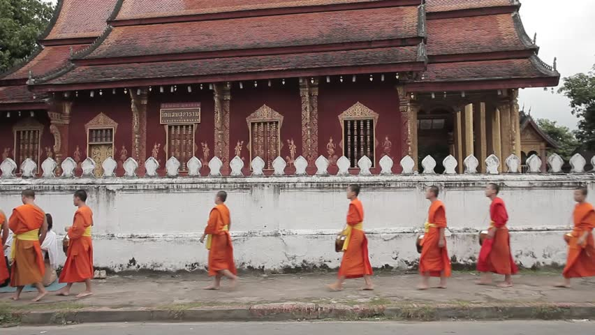 LUANG PRABANG, LAOS - OCTOBER 18: Buddhist Monks collecting morning offerings on October 18, 2009 in Luang Prabang, Laos. Processions like these are seen a over the town from sunrise.