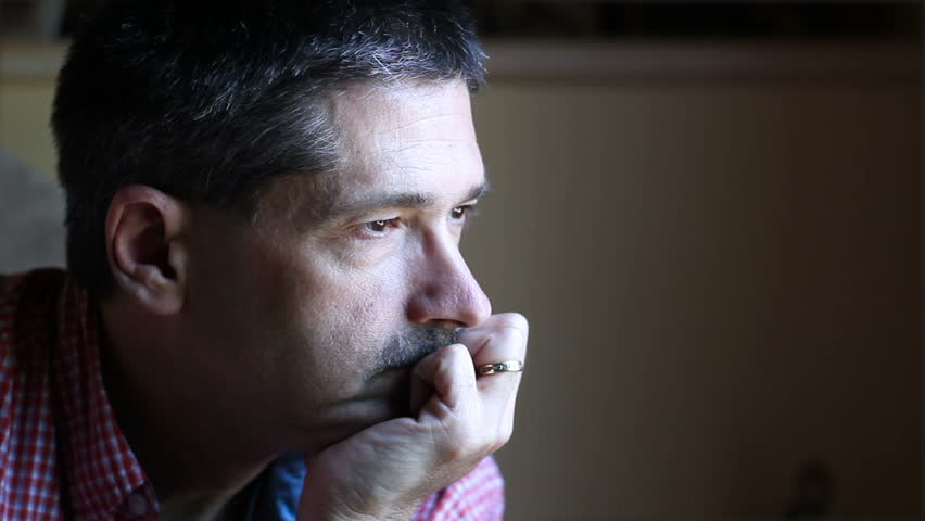 Portrait of depressed middle aged man staring out a window