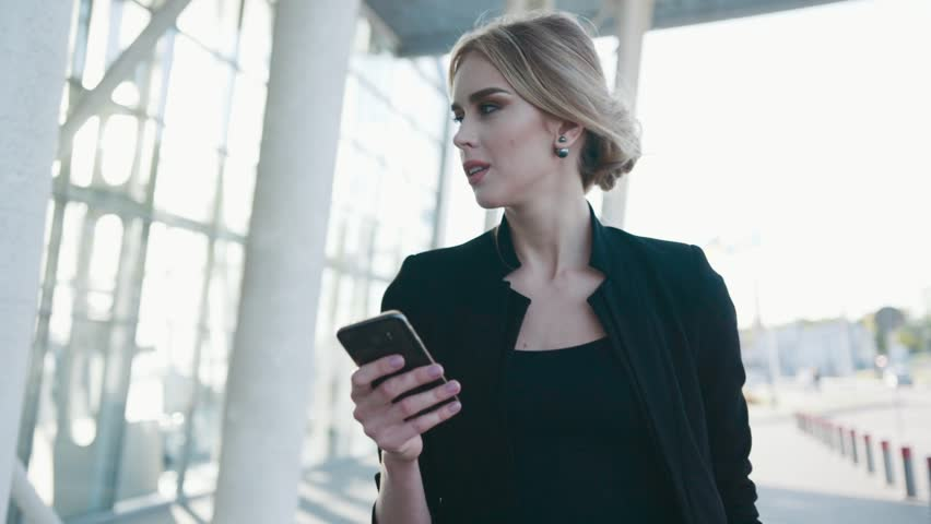 Gorgeous European businesswoman with formal hairstyle in a hurry passes the airport terminal, texts the message on her phone, looks around. Fashionable outfit. Business class, luxurious lifestyle.