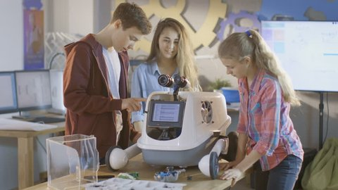 Two Girls and a Boy Turn On Fully Functional Programmed Robot with Bright LED Lights for School Science Class Project. Shot on RED EPIC-W 8K Helium Cinema Camera.