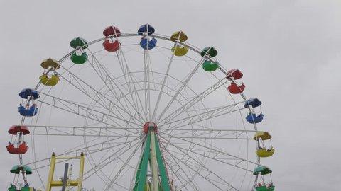 Underside view of a ferris wheel over blue sky. UltraHD stock footage.