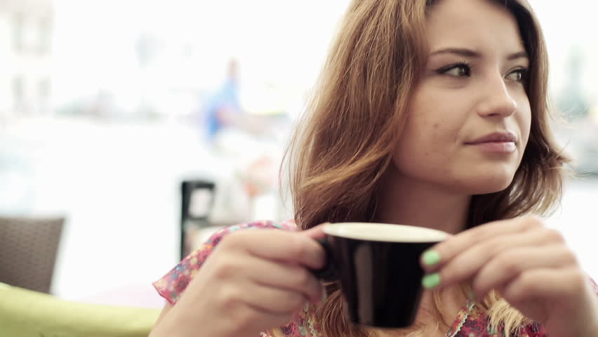 Young attractive woman drinking coffee in cafe, steadicam shot