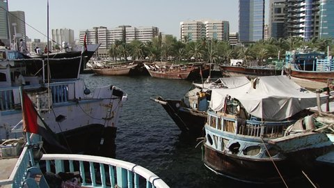 DUBAI, UAE - CIRCA 2008: Pan-right across the Dhow Wharfage area on the banks of Dubai Creek north of Maktoum Bridge. Hundreds of traditional dhows are docked waiting to load and unload diverse cargo.