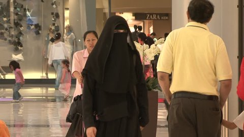 UAE - CIRCA 2008: Pan-right shot of woman in niqab walking in a mall. Niqab is the type of hijab that covers the face leaving only a slit for the eyes. It is a Muslim tradition to show modesty.