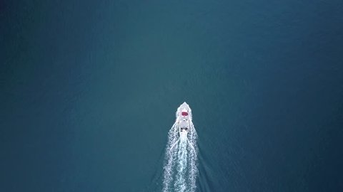 Aerial birds eye view of a ferry boat traveling in the blue Pacific ocean. Leaves a wake behind it. smooth glassy water.