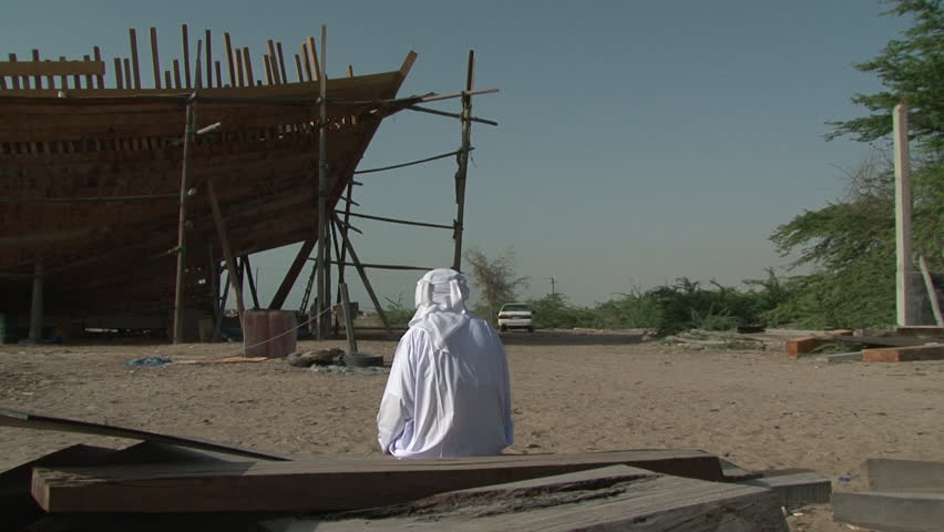 UAE - CIRCA 2008: Pan-left rear-POV of an Emirati man sitting in a traditional ship building yard on the seashore looking at a a dhow being constructed.