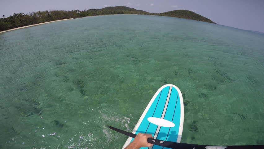 POV man standing on a paddle board in tropical waters Young man on a paddle board on the sea. Point of view, high shot