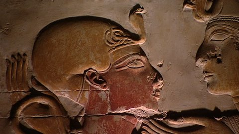 ABYDOS, EGYPT - CIRCA 2002: Zoom-out from the head of 19th Dynasty Pharaoh Seti I looking at the goddess Isis to reveal her sun-disc-in-horns head-dress. Temple of Abydos.
