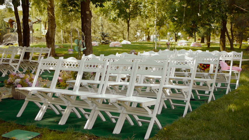 White Wooden Chairs. Wedding Aisle Decor. Outdoors Wedding Ceremony, Many  Flowers, Floristry