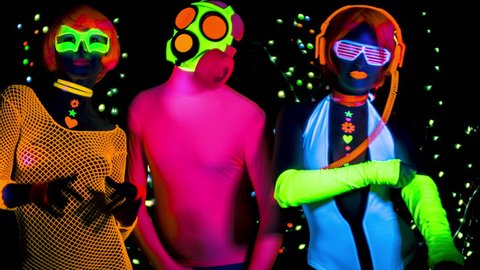 4k fantastic video of 3 sexy cyber glow ravers filmed in fluorescent clothing under UV black light. 2 cool women and a guy in a gasmask.