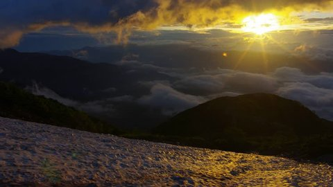 Sunrise above sea of clouds and snowy valley