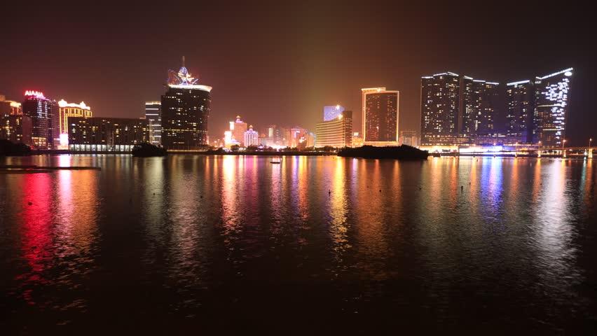 Macau, China - December 9, 2016: Cityscape time lapse with Wynn Macau, MGM Macau, Casino Lisboa and Grand Lisboa Hotel reflected in Nam Van Lake, a man-made lake in southern end of Macao Peninsula.
