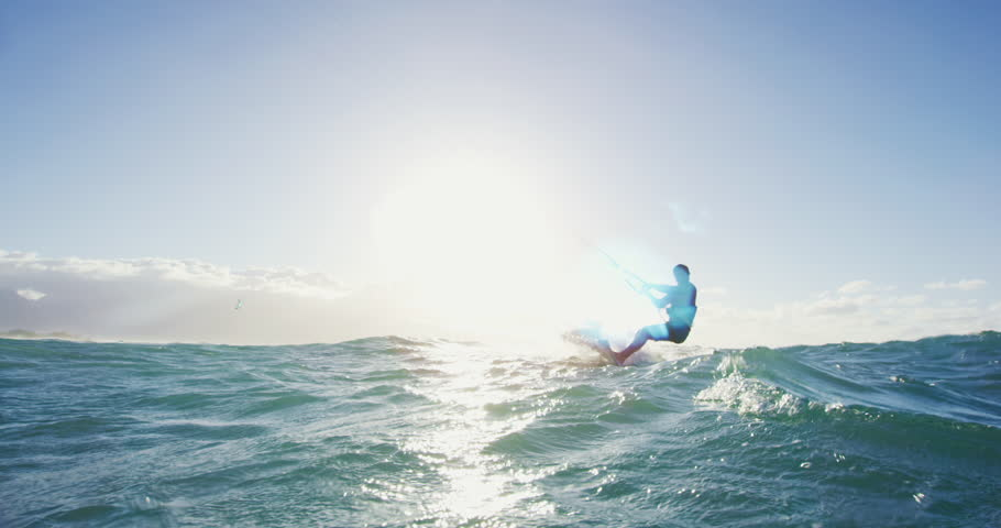Young man kite surfing in blue ocean at sunset. Having fun outside in nature. Extreme sports summer. Shot on RED | Shutterstock HD Video #27427804