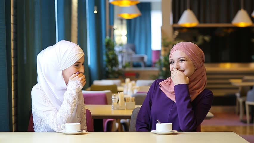Two beautiful young Muslim women in a cafe communicate and laugh
