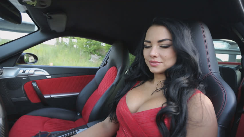 Hot brunette in glasses sits at the wheel of a sports red car, the brunette in a red evening dress is about to leave, a nice summer day