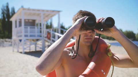 A beach lifeguard with a bare torso looks through binoculars watching suspicious personalities.In Slow Motion/