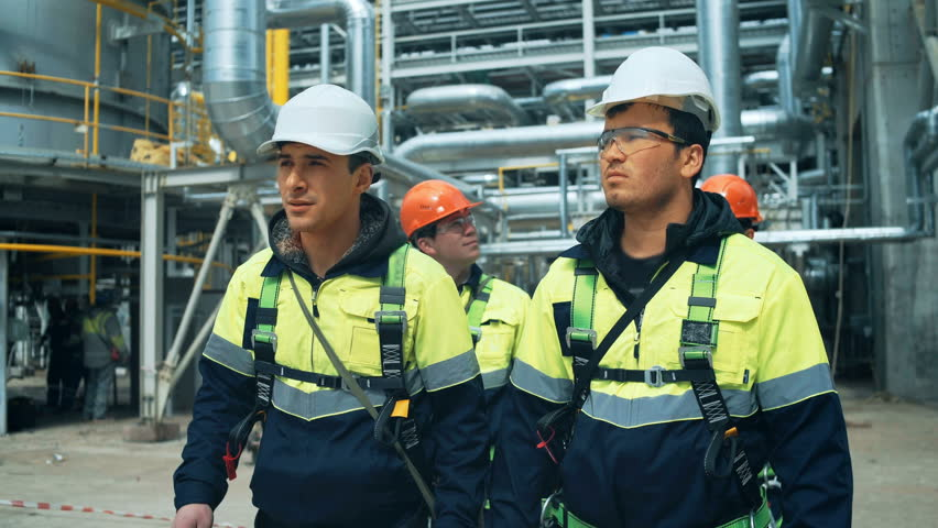Team of workers walking on industrial factory