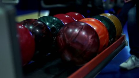 Male hand a bowling player touches bowling balls slow motion. Close up player chooses a bowling ball. Bowling game