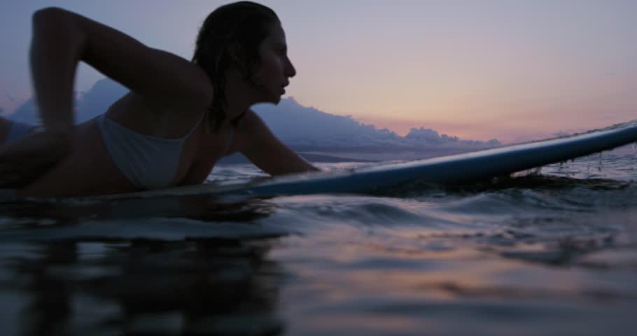 Beautiful young woman paddling surfboard in bikini at sunset. Shot on RED | Shutterstock HD Video #27530104