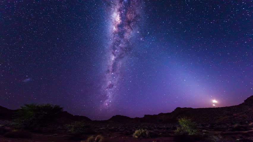 The apparent rotation of an outstandingly bright Milky Way and starry sky beyond the mountains of the Namib desert, Namibia. Time Lapse.