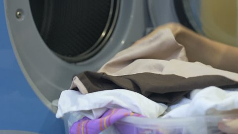 Household woman carefully loading dirty clothes from basket to washing machine