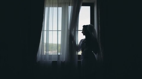 Silhouette of young bride in white peignoir staying near window. Woman looks at distance, morning before wedding.